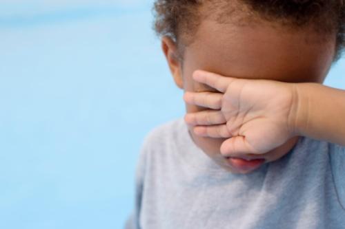 Boy hiding his eyes